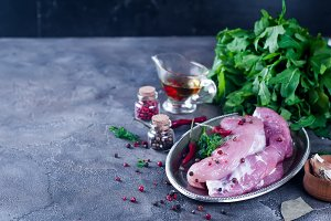Raw fresh meat steak entrecote and seasonings in the iron plate with oil, chili, spices dill