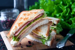 Club sandwich with a salad on  wooden plate