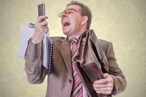 Angry businessman screaming at phone