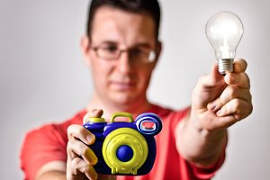 Man hold toy camera and light bulb