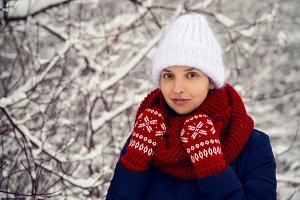 smiling girl in a knitted red scarf, white  hat and  mittens