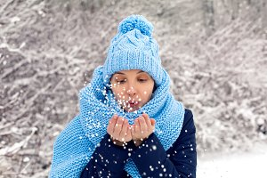 young girl in blue knitted hat, scarf blows snow