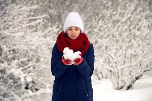 young girl in white knitted hat, red scarf and mittens blows snow