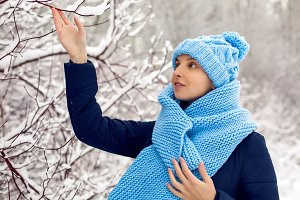 smiling girl in a knitted blue scarf, and cap stands