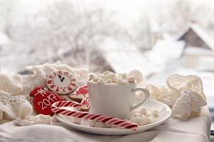 white Cup of cocoa on a saucer, marshmallows and candy