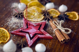 red wooden star lies with dried orange, cinnamon and meringue