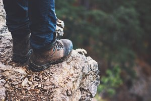 Feet boots on rocky cliff