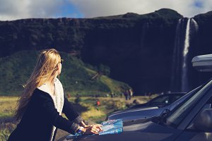 girl near car with map travel