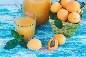 Apricot juice and fruits in the basket with mint