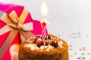 Birthday cake with candle and a gift on a white background