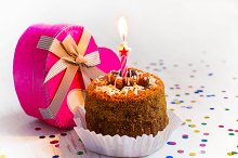 Mini cake with one candle and a gift in a box in the shape