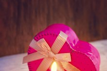 Birthday cake with candle and a gift on the old wooden background