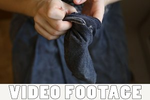 A woman sews up holes in socks