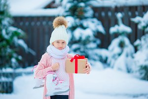 Adorable little girl wearing warm clothes outdoors on Christmas day holding gift and skates