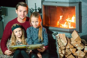 Father and his two little kids sitting by a fireplace in their family home on Xmas eve