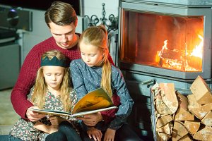 Father and his two little kids reading book and relaxing by the fire place some cold evening onChristmas eve