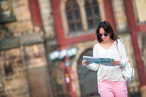 Young woman with touristic citymap in old european city. Happy girl enjoy vacation holiday in Europe.