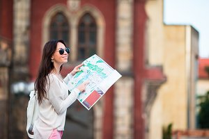 Young woman with a city map in city. Travel tourist girl with map in Prague outdoors during holidays in Europe.
