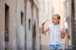 Adorable little girl outdoors blowing soap bubbles in european city. Portrait of caucasian kid enjoy summer vacation in Italy