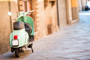 Light blue scooter on the street of the old city. Old classic european city elements