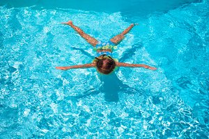 Little cute happy girl swimming in outdoor pool like a star