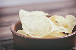 Close-up of a dish with chips standing on dark gray colored wooden table. Vertical studio shot