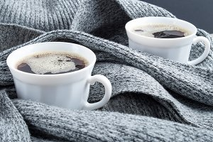 Cups of coffee wrapped in scarf