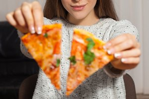 woman is eating delicious pizza