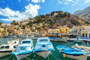 Traditional Greek fishing boats in harbour at Symi Town in the Dodecanese Greece Europe