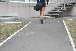 Young fitness woman in sportwear going on stairs up to gym to training. Girl going to health club for workout. Close up