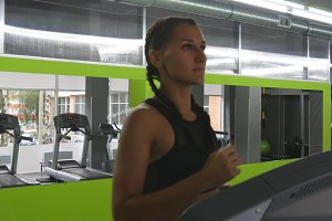 Young strong woman with perfect fitness body in sportswear running on treadmill in gym. Girl exercising during cardio workout. Female training indoor at sport club. People jogging. Close up