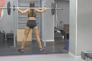 Young woman holding a barbell with heavy weights on her shoulders as she squats. Strong girl training in the gym. Beautiful female athlete exercising at health club. Close up. Active lifestyle