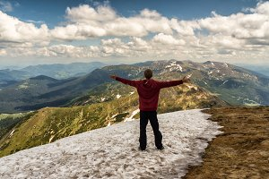Young man standing with raised hands on top of a mountain and enjoying vview