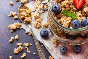 Homemade muesli granola in a jar on rusty black table