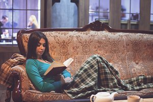 woman with plaid  is reading a book