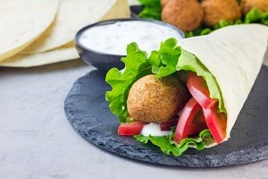 Chickpea falafel balls with vegetables and sauce, roll sandwich preparation, horizontal, copy space