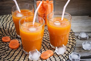 Glasses with carrot juice on a wooden background