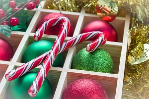 Preparation for Christmas: festive balls and candy cane in wooden box, light white frame, horizontal