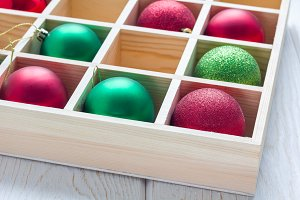 Preparation for Christmas: festive balls in wooden box on white wooden table, horizontal