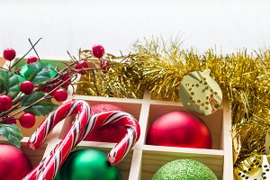Preparation for Christmas: festive balls and candy cane in wooden box, horizontal, copy space