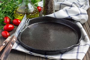Empty cast iron skillet on wooden table, vegetables and spices on background, horizontal, copy space