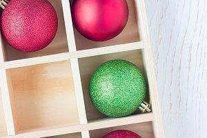 Preparation for Christmas: festive balls and candy cane in wooden box on white wooden table, vertical, copy space