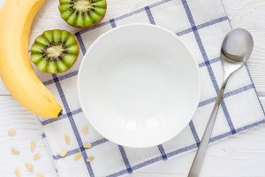 Empty bowl for breakfast, fruits, nuts and spoon on background, top view, copy space