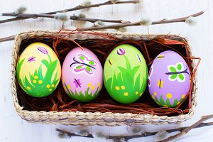 Painted Easter eggs in a wicker box on a white background.