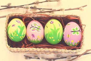 Painted Easter eggs in a wicker box on a white background. tinte