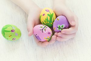 Painted Easter eggs with spring pictures in a child's hands