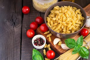 Pasta, herbsl and cherry tomatoes on old wooden background. Conc