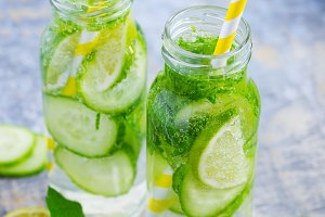 Lime, cucumber lemonade in bottles with straws