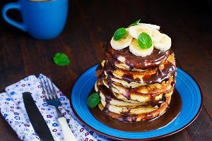 Pancakes with banana and chocolate on blue plate
