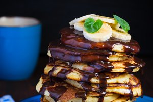 stack of pancakes with chocolate topping and banana